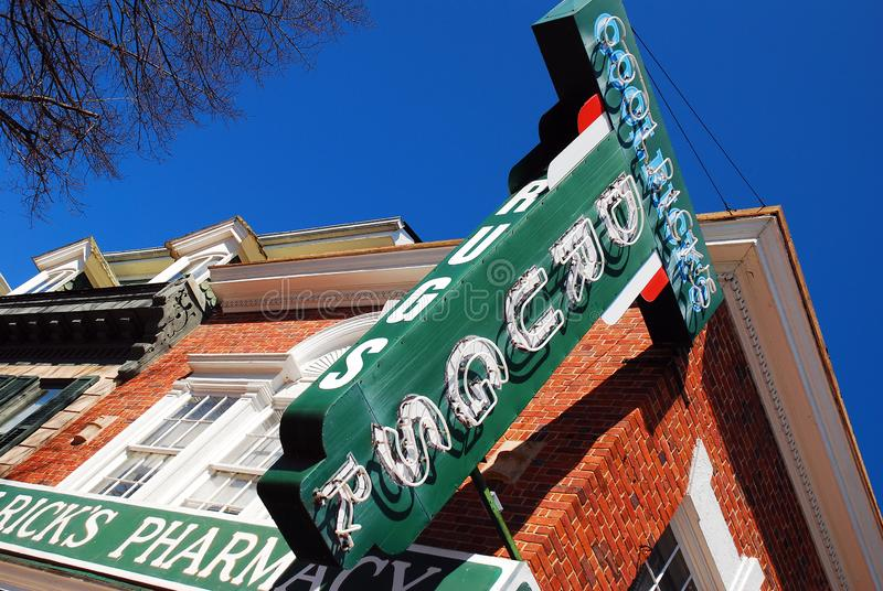A large sign looms over an old fashioned pharmacy stock photo