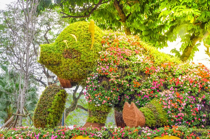 A large sitting and smile pig statue decorated with beautiful flowers and colorful flowers in a park in Hanoi, Vietnam stock photography