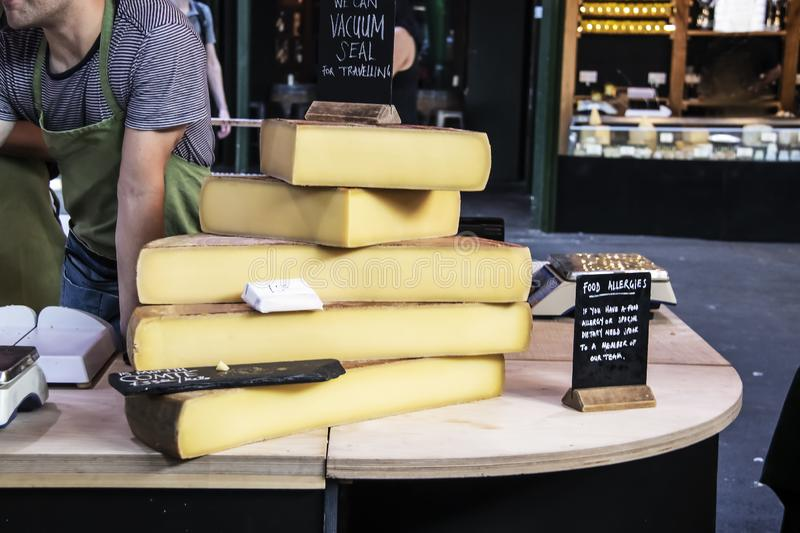 Large slabs of cheese on wooden table at a market with worker leaning over talking to customer and food allergies sign on tables. With scales and another stall royalty free stock image