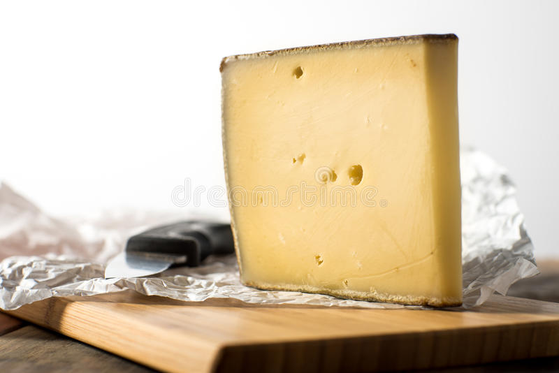 Large slice of Gruyere French Cheese. French Gruyere cheese sliced on wooden board stock images