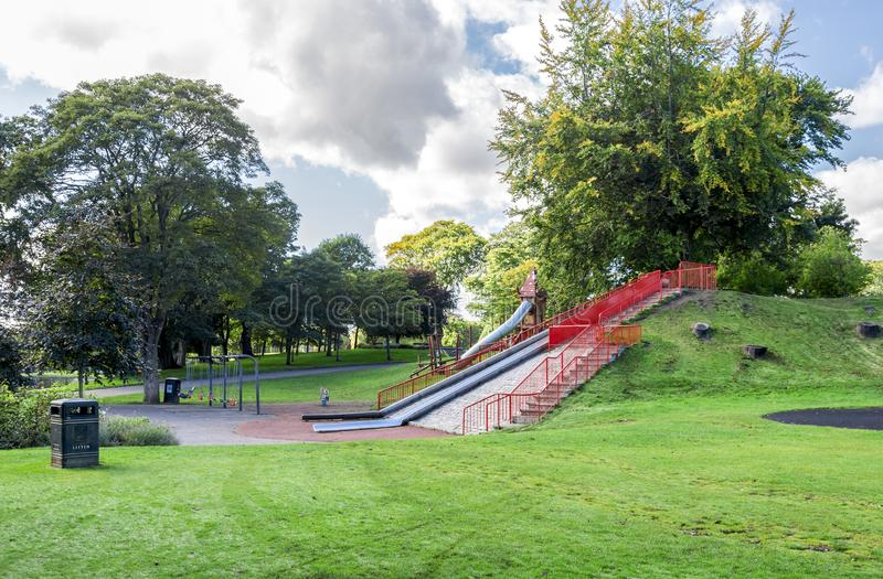 A large slide on a small hill and several swings at the entrance to Duthie park near Dee river, Aberdeen royalty free stock image