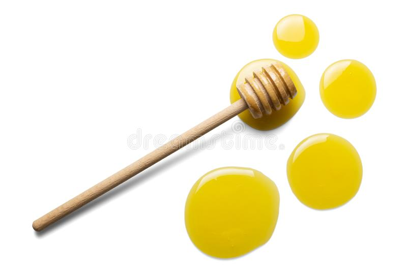 Large and small drops of fresh honey, wooden stirrer isolated on white stock image