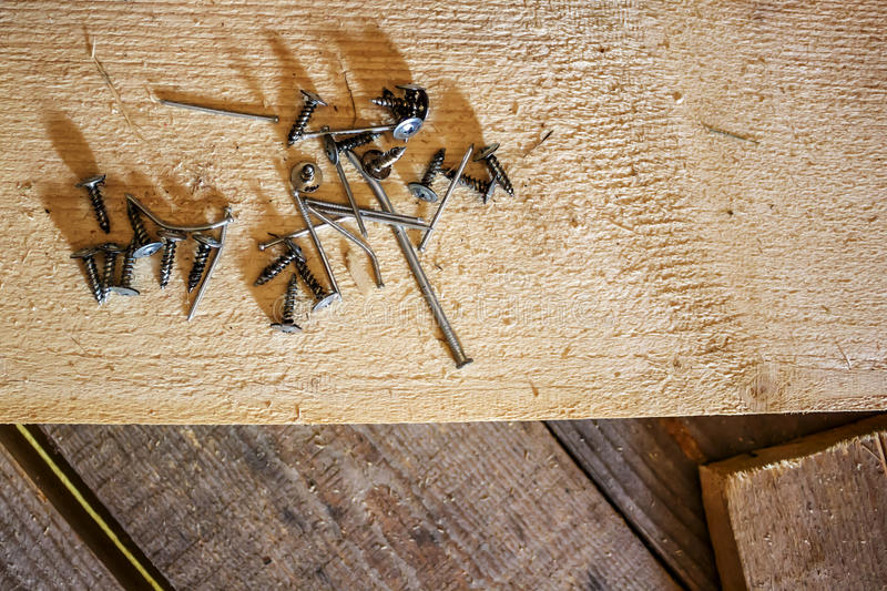 Large and small nails, screws - scattered. On a brutal wooden background stock images