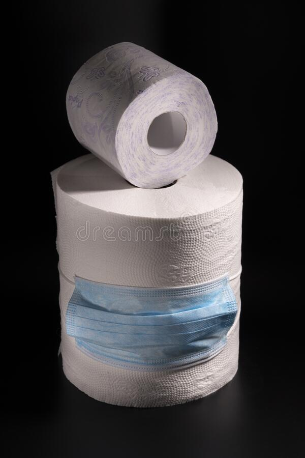 Large and small roll of toilet paper or paper towels with a medical mask on a black background. Close-up stock photos