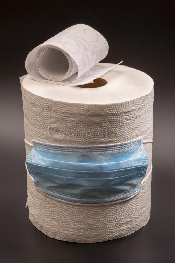 Large and small roll of toilet paper or paper towels with a medical mask on a black background. Close-up stock image
