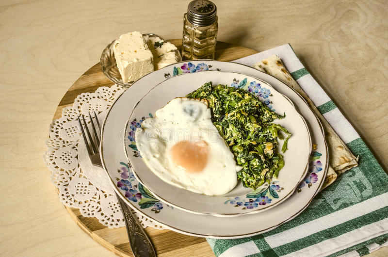 Large and small snack barsporcelaindishes with spinach and fried eggs royalty free stock images