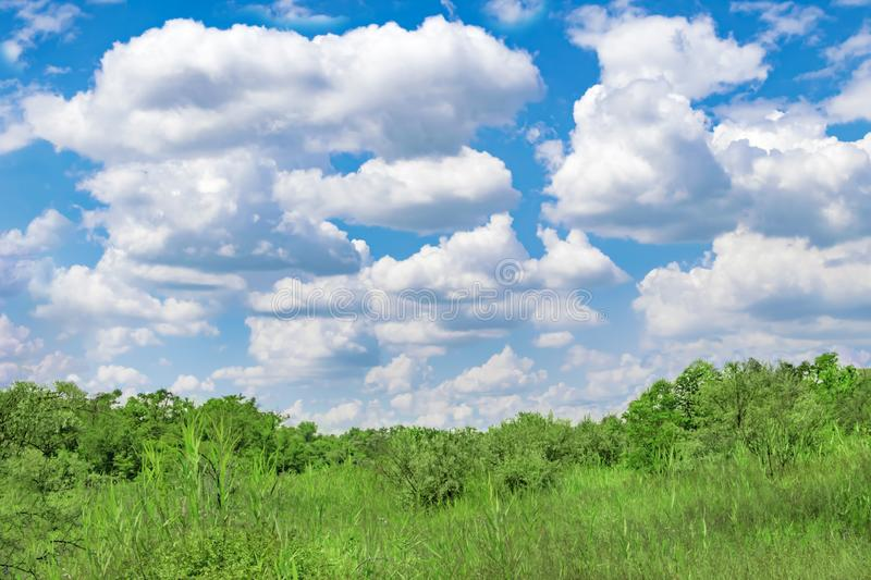 Large and small white clouds on background of blue sunny summer sky and green hills with trees, bushes and grass stock photography