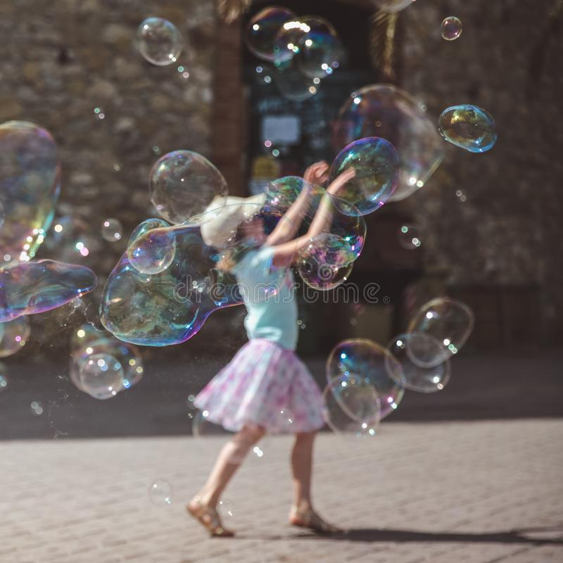 Large soap bubbles fly in the air outside. Girl playing in the background in summer day royalty free stock image