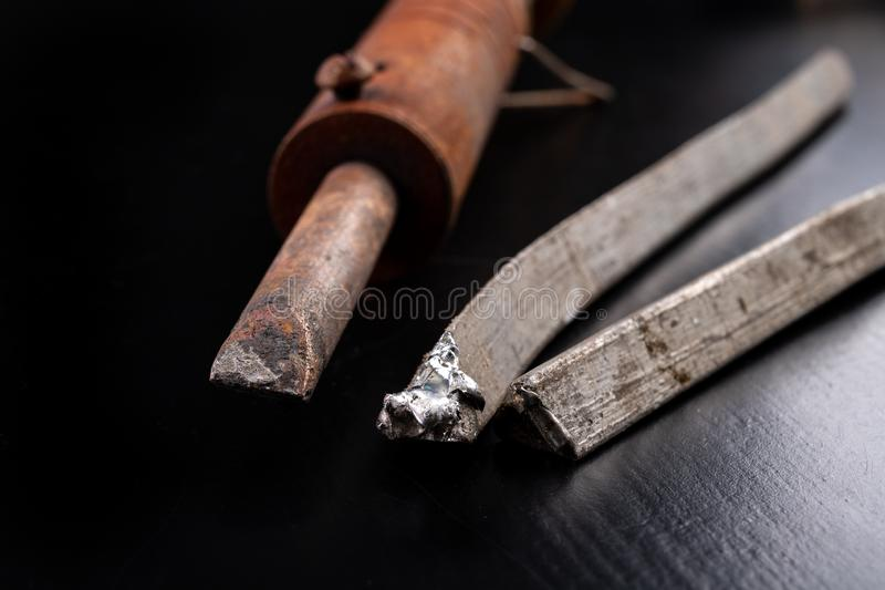 A large soldering iron and soldering accessories on a workshop table. Connecting sheets using soldering. Dark background, blue, board, brazing, circuit stock images