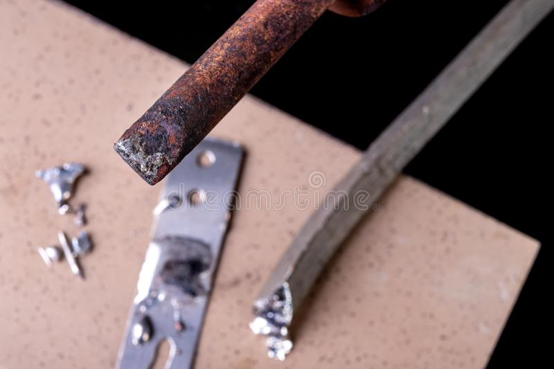 A large soldering iron and soldering accessories on a workshop table. Connecting sheets using soldering. Dark background, blue, board, brazing, circuit stock photo
