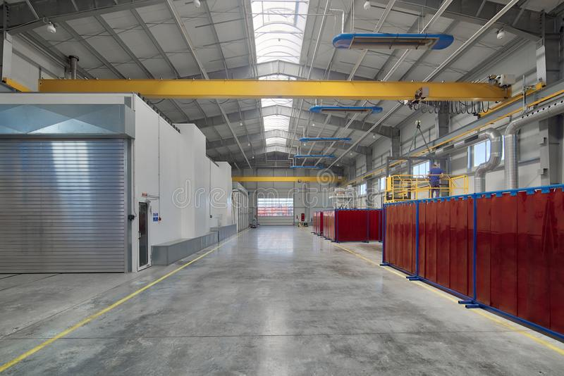 Large, spacious and light factory workshop. Large spray booth inside the workshop royalty free stock images