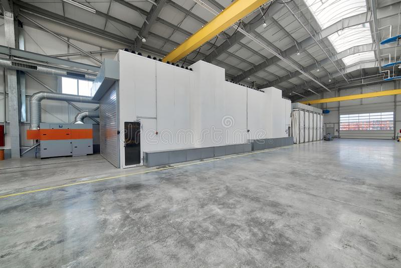 Large, spacious and light factory workshop. Large spray booth inside the workshop royalty free stock photography