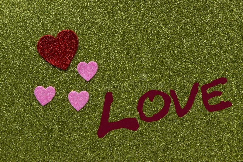 Red and pink sparkly hearts on green background that says Love, royalty free stock photos