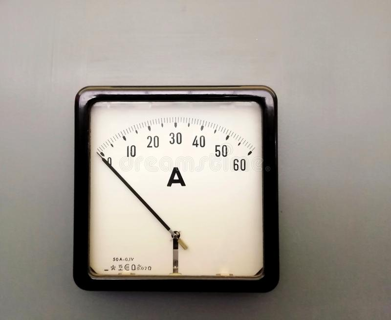 a large square industrial ammeter with an analogue dial with numbers with standard electrical symbols on a white dial on a grey royalty free stock image