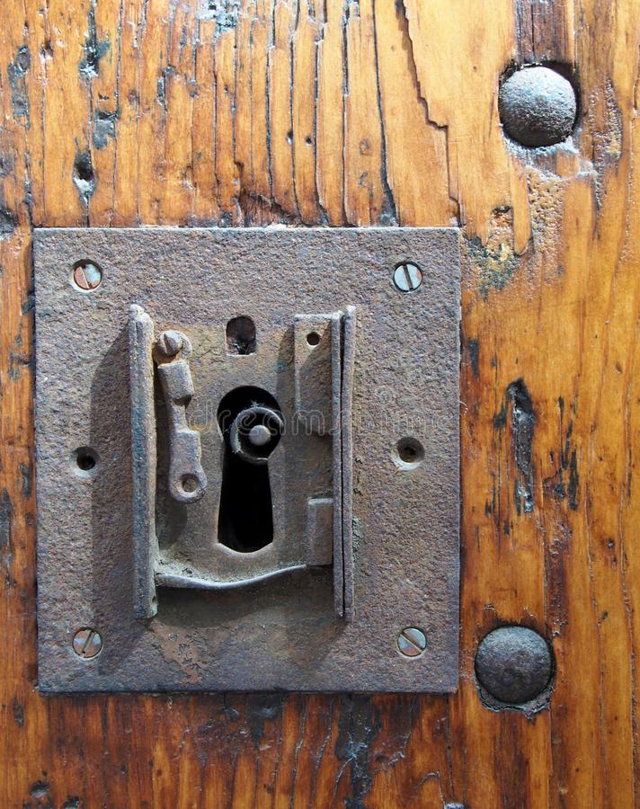 Large square rusty iron lock with keyhole in an old varnished wooden door with the end of the key visible and metal rivets. A large square rusty iron lock with stock images