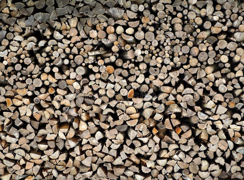 Large stack of chopped trunks and branches. Firewood background and texture. royalty free stock photo