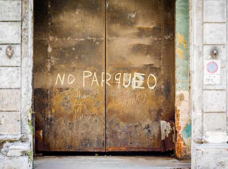 Large steel rusty doors in Havana, Cuba with no parqueo sign. No parking royalty free stock photo