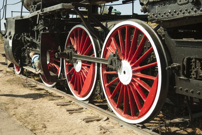Large steel wheels of old steam locomotive red with white outline royalty free stock photo
