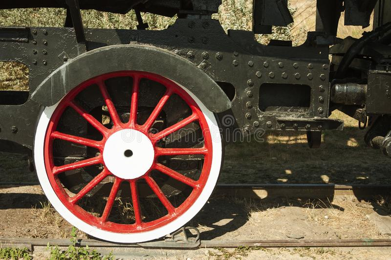 Large steel wheels of old steam locomotive red with white outline royalty free stock image