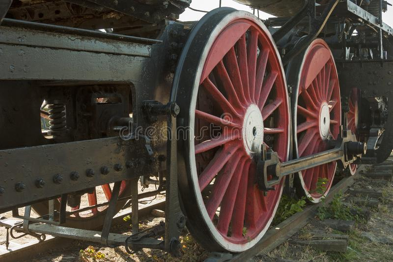 Large steel wheels of old steam locomotive red with white outline stock photo