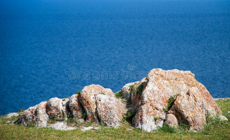 Large stone boulders on the sea shore against the sea background stock photos