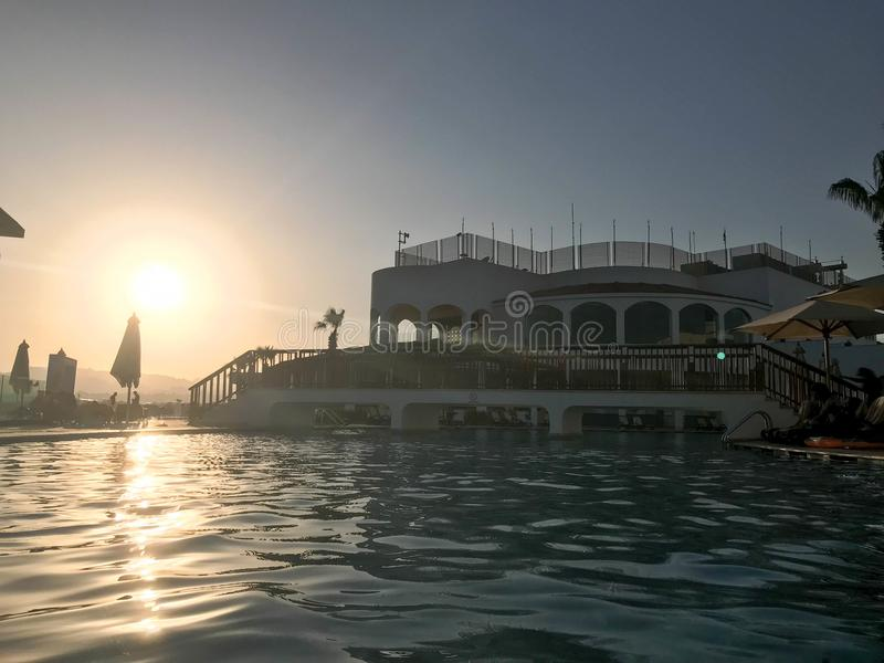 A large stone building near the water, a pool against the blue sky and a big sun, a sunset in the evening in a tropical seaside re royalty free stock photos