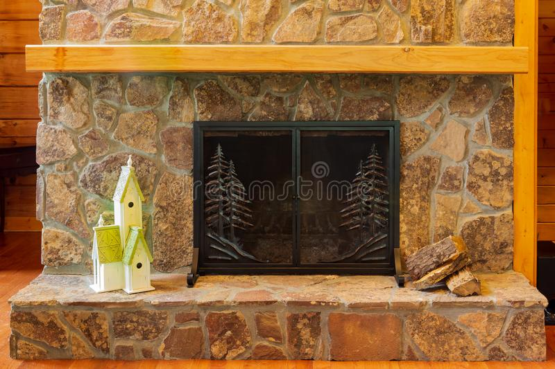 Stone fireplace with birdhouse on the hearth and wood ready for the fire. royalty free stock photos