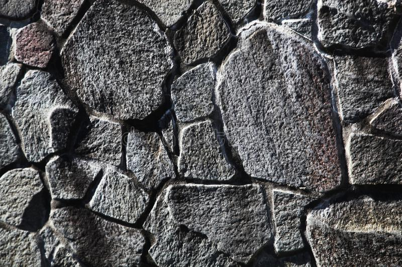 Stone wall with rough textures arranged together. Large stone wall in grey with rough textures arranged nicely together royalty free stock photo