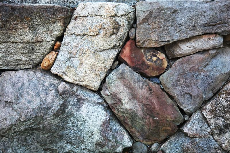 Stone wall with rough textures arranged together. Large stone wall in grey with rough textures arranged nicely together royalty free stock image