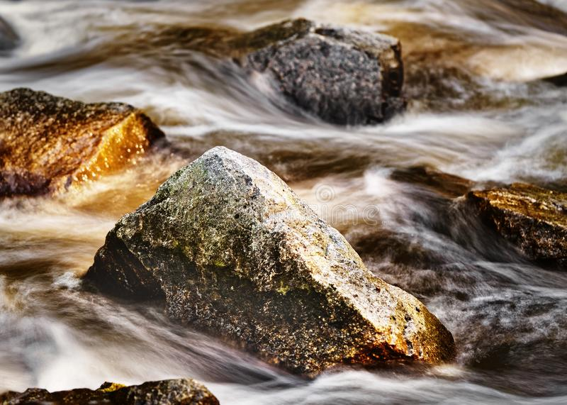 Large stones in flowing water at evening light. Large stones in the flowing water at evening light, water movement in long exposure - Location: Germany, Saxony royalty free stock photography
