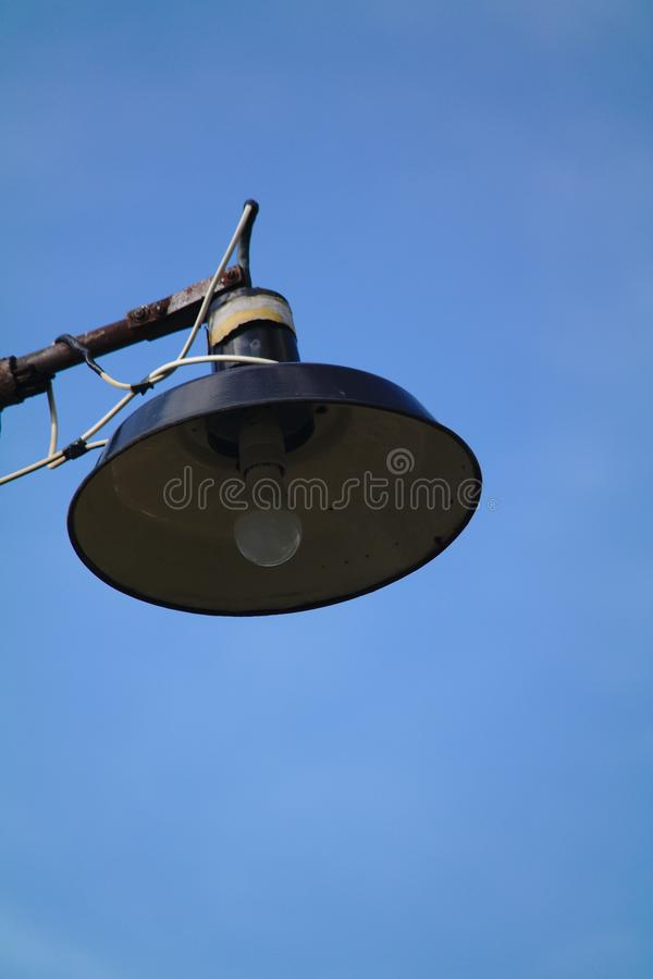 A large street lamp like a UFO on the background of blue sky. Design, urban, post, black, white, light, object, decorative, architecture, metal, city, town stock photos