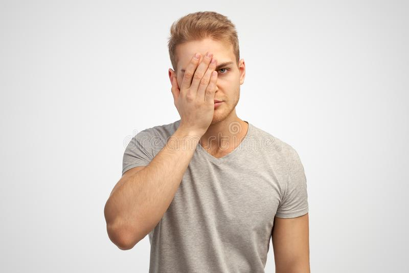 Large Studio portrait of a young light man t-shirt covering his face with a palm in the sign facepalm. royalty free stock image