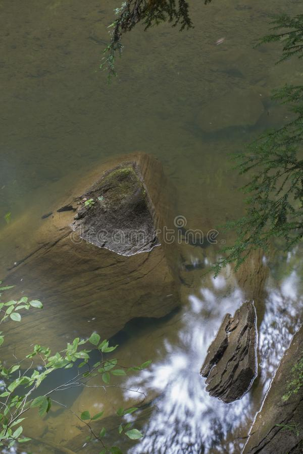 Large submerged rock. A large rock in a stream with a small portion breaking the surface in Hocking Hills State Forest at the Old Man`s Cave area near Logan stock photo