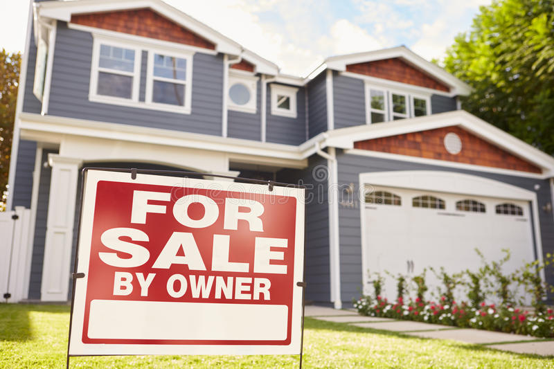 Large suburban house with �for sale� sign displayed outside royalty free stock photo