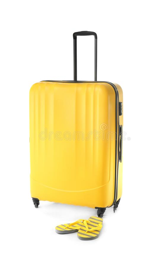 Large suitcase and flip-flops on white background royalty free stock images