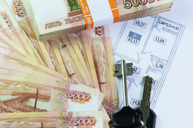 A large sum of Russian money and the keys are on the plan of the apartment. Purchase of housing stock photos