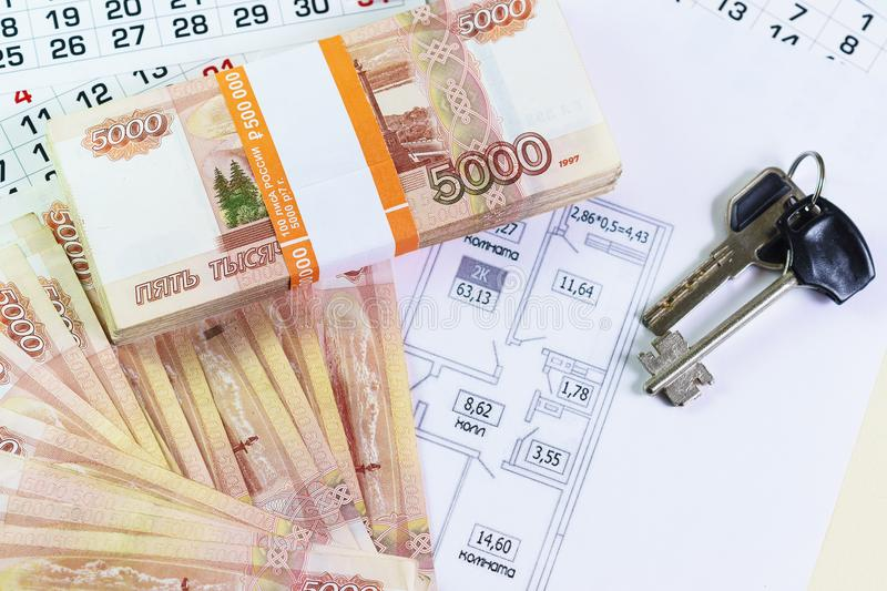 A large sum of Russian money and the keys are on the plan of the apartment. The leaves of the calendar. Time to buy stock photography