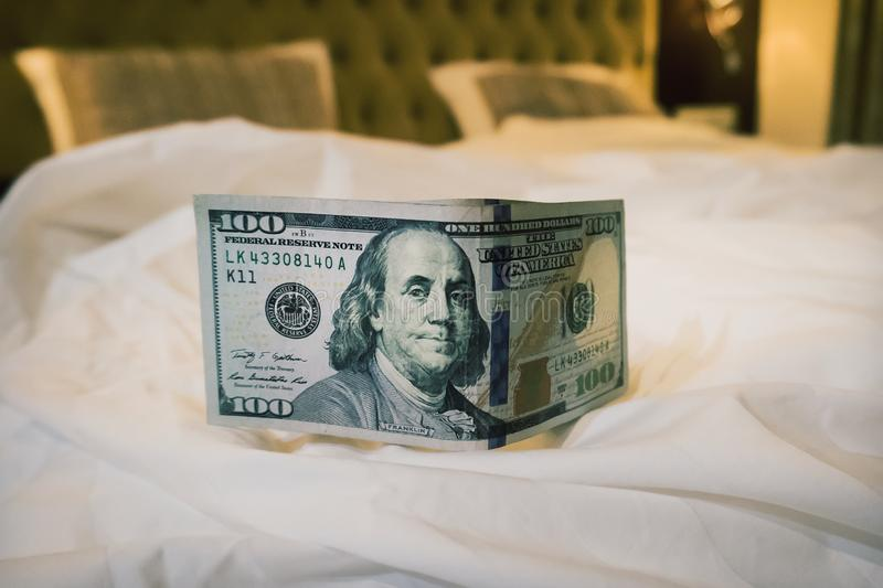 a large sum of us dollars on the table on a blurred bed background. royalty free stock photography