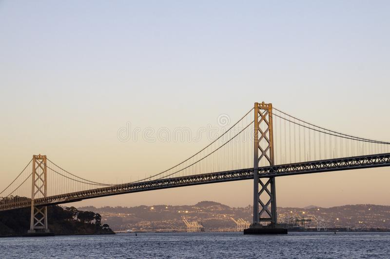 Large suspension bridge over a body of water. At sunset with cityscape in the background d stock photos