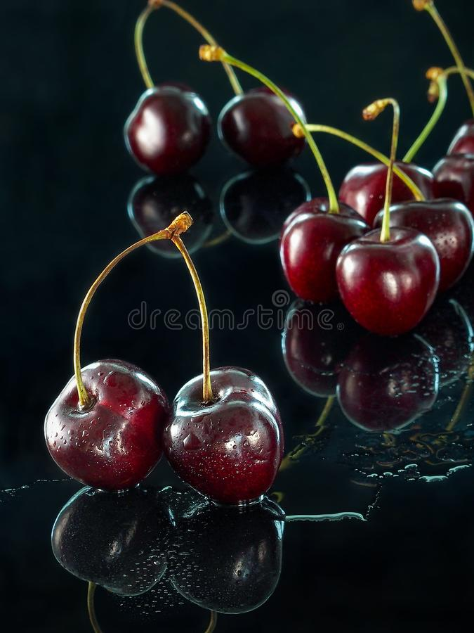 Large sweet cherry reflected on a dark mirror surface stock photos