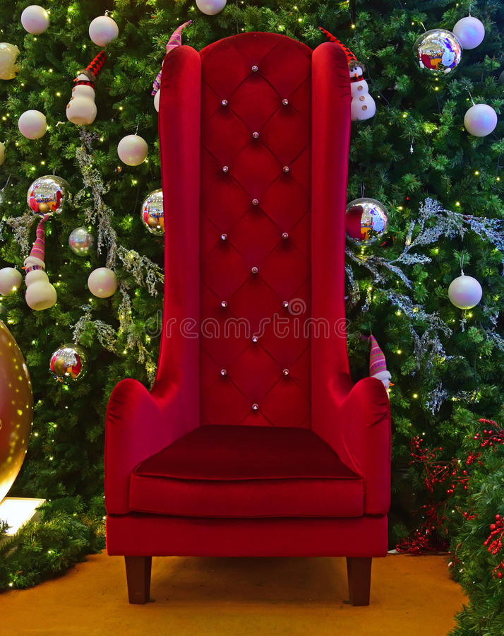 Large tall chair for Santa Claus with Green Christmas Tree in the background. Santa Claus Christmas maroon red smooth velvet large tall chair for Gift stock photography