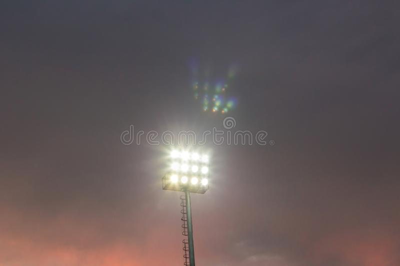 Large tall high outdoor stadium spotlights on rigid frame construction under natural sunlight. Spotlights tower in the stadium twilight time royalty free stock photos