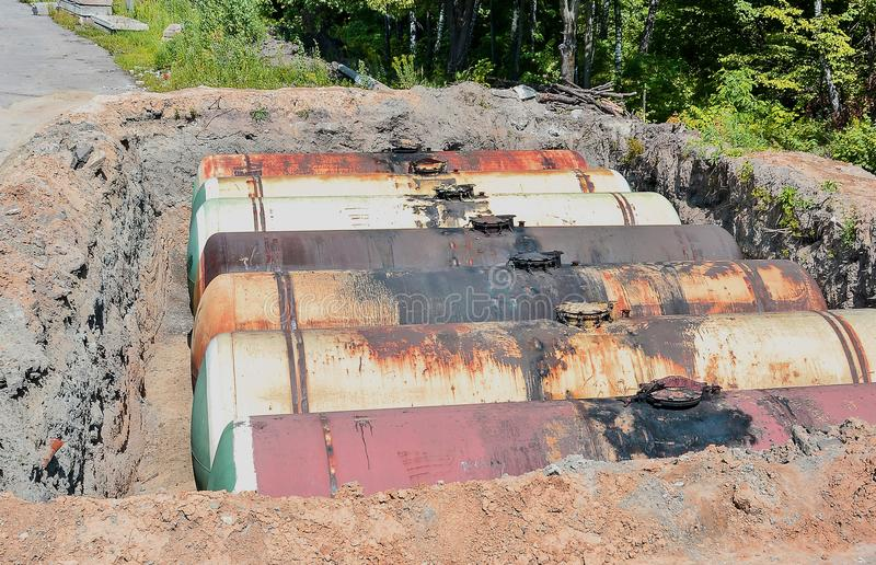 Large tank for gasoline in the excavated quarry for storage of petroleum products stock photography