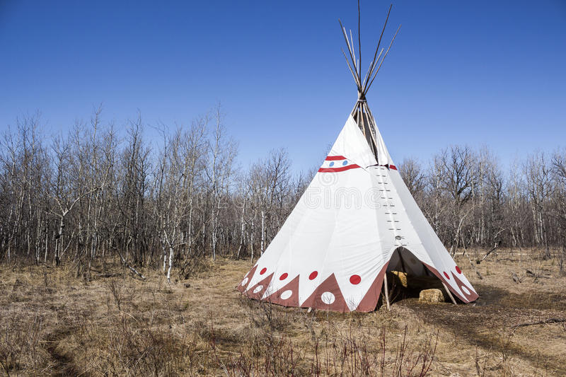 Large teepee sitting in a field of dead grass royalty free stock photography