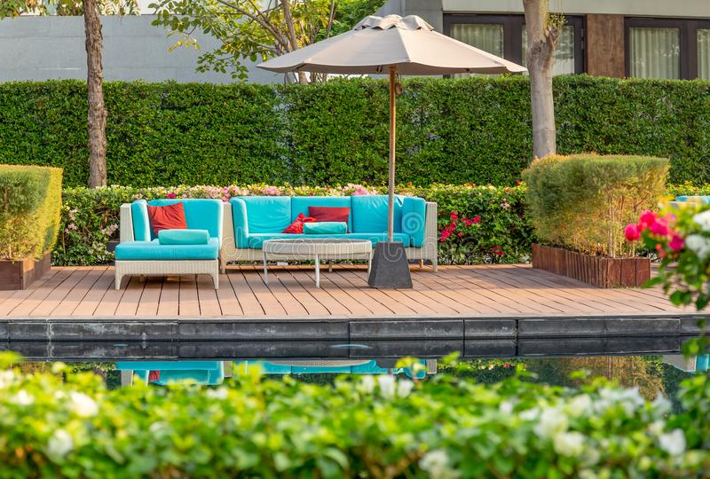 Large terrace patio with rattan furniture in the garden with umbrella. Large terrace patio with rattan furniture in the garden with umbrella stock photos