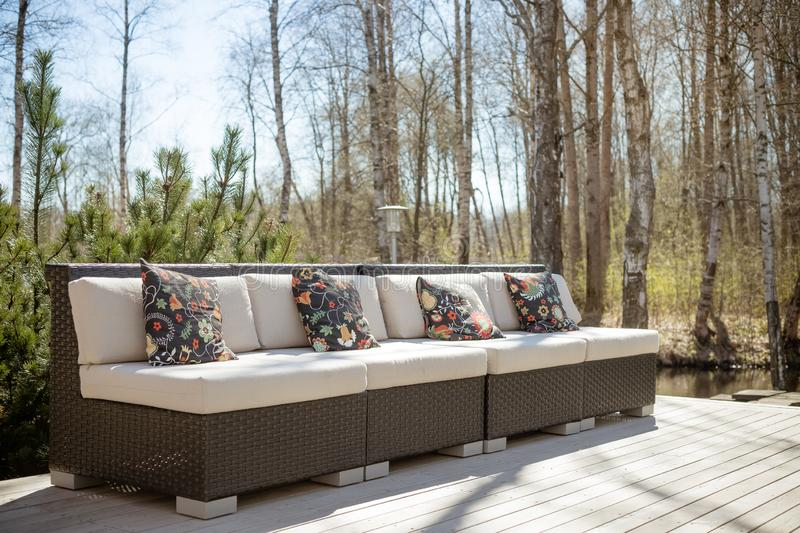 Large terrace patio with rattan garden furniture set.Wooden garden lounge chair with cushion. comfortable rattan sofa. relaxing royalty free stock photos