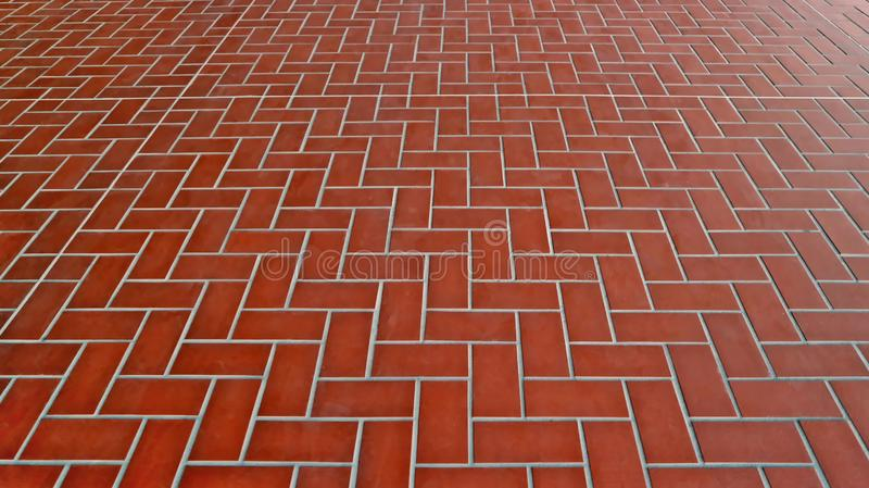 Large terracotta tiled pavement with herringbone pattern. Background and texture stock images