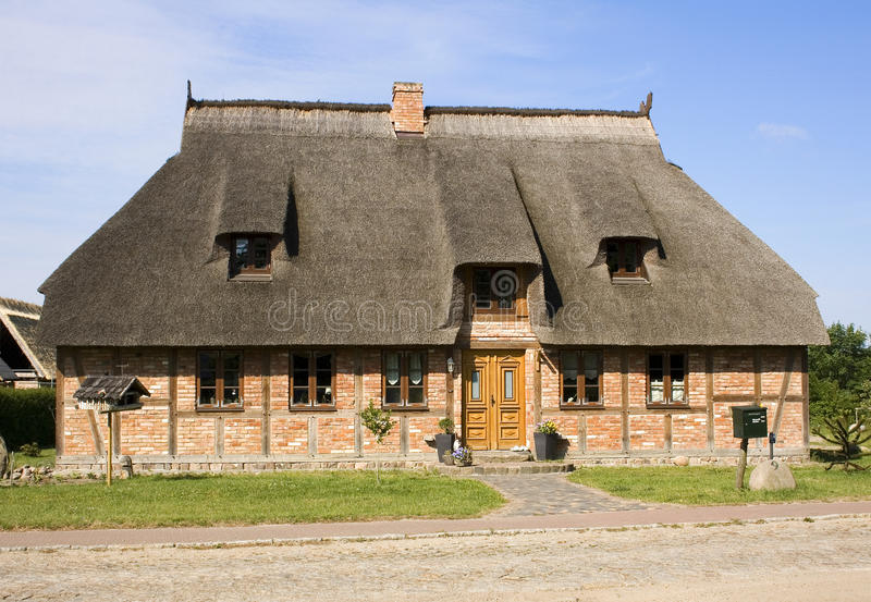 Large thatched cottage. Exterior of large thatched cottage in countryside royalty free stock images