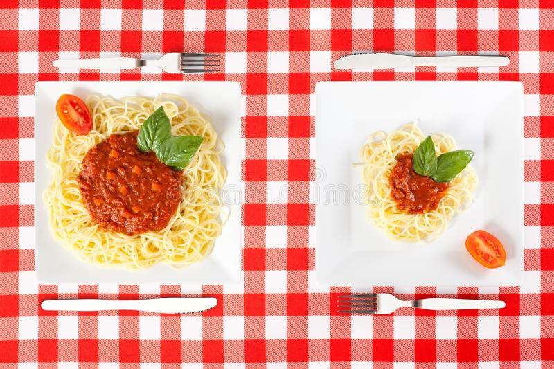 Large and tiny food portions. Contrasting large and tiny food portions of Spaghetti royalty free stock photography