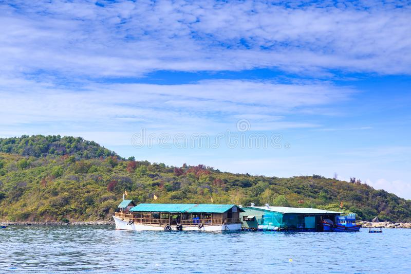 Tourist Motorboat at Moorage near Green Coast Clouds Sky. Large tourist motor-boat at moorage near green hills shore against white clouds lace in blue sky royalty free stock photography